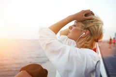 Pretty hipster girl with closed eyes resting on pier near sea during her long-awaited vacation Royalty Free Stock Images