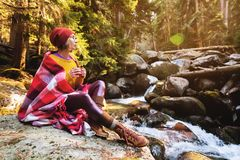 A pretty hipster girl with a plaid plaid on her shoulders in a hat and a yellow sweater and glasses with a mug of coffee. In her hands looks at a mountain river royalty free stock image