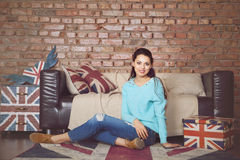 Pretty hipster girl sitting near the couch at home Royalty Free Stock Photo