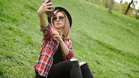 Girl Taking Selfie. Pretty Hipster Girl Sitting In Park And Taking Selfie On Vitage Camera stock video