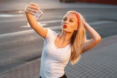 Pretty hipster girl taking selfie and making duck face. Sending. Kisses. Instagram photo Stock Photography