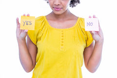 Pretty hipster holding yes and no sheets of paper. On white background Royalty Free Stock Photo