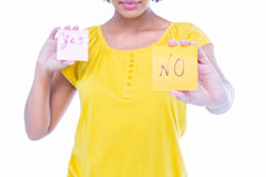 Pretty hipster holding yes and no sheets of paper. On white background Stock Photos