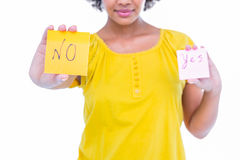 Pretty hipster holding yes and no sheets of paper. On white background Royalty Free Stock Image