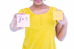 Pretty hipster holding yes and no sheets of paper. On white background Royalty Free Stock Images