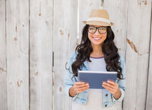 Pretty hipster smiling at camera holding tablet Stock Image