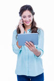Pretty hipster talking on the phone holding tablet Stock Photo