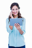 Pretty hipster talking on the phone holding tablet Stock Image