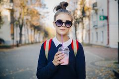 Pretty hipster teen with red bag drinks milkshake from a plastic cup walking street between buildings. Cute girl in stock photos