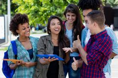 Pretty hispanic female student learning with group of latin and african american young adults stock photos