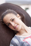 Teenage girl leaning on her horse Royalty Free Stock Images