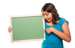 Pretty Hispanic Girl Holding Blank Chalkboard. Pretty Hispanic Girl Pointing and Holding Blank Chalkboard Isolated on a White Background Royalty Free Stock Photos