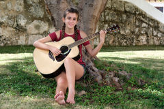 Pretty hispanic teenage girl playing an acoustic guitar. Sitting on the grass stock images