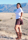 Pretty Hispanic Woman. Photo of pretty hispanic woman in white blouse and pleated skirt with  mountains in the background Stock Photo