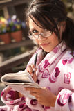 Pretty Hispanic Woman in Bathrobe with Newspaper Royalty Free Stock Image