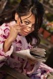 Pretty Hispanic Woman in Bathrobe with Newspaper stock photography
