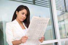 Pretty Hispanic Woman Reading Newspaper Royalty Free Stock Image