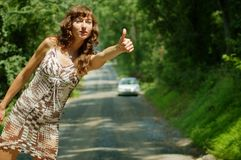Pretty Hitch Hiker. Pretty girl hitching hiking on country road stock photography