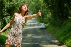 Pretty Hitch Hiker. Pretty girl hitching hiking on country road royalty free stock images