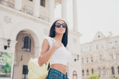 Pretty hot mulatto model in trendy fashionable sunglasses and white cap on the stroll in town with architecture. Bare fit abs, ni stock image