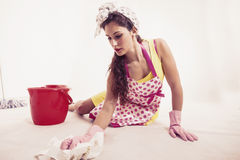Pretty housemaid with cloth and bucket cleaning the floor Stock Photography