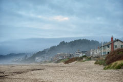 Pretty houses and people near sea in USA. Marvelous Cannon beach near buildings and trees on background Royalty Free Stock Photos