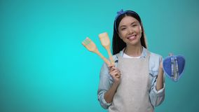 Pretty housewife in apron holding kitchenware and smiling at camera, cooking. Stock footage stock video