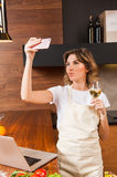 Pretty housewife with cellphone in the kitchen Royalty Free Stock Photo