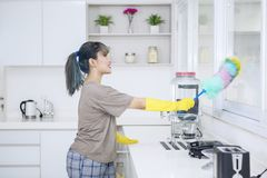 Pretty housewife is cleaning windows in kitchen. Portrait of pretty housewife is cleaning windows with a duster brush and standing in the kitchen royalty free stock photo