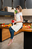 Pretty Housewife in the kitchen sitting on table Royalty Free Stock Photo