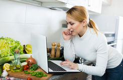 Pretty housewife looking in internet for recipe Royalty Free Stock Image