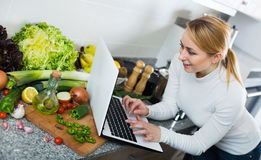 Pretty housewife looking in internet for recipe of vegetables Stock Image