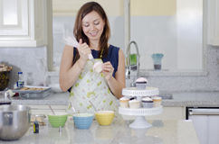 Pretty housewife making cupcakes Royalty Free Stock Photos