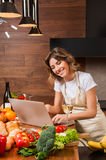 Pretty housewife reading from her laptop and drinking wine Royalty Free Stock Photos