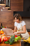 Pretty housewife reading from her laptop and drinking wine Royalty Free Stock Image