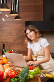 Pretty housewife reading from her laptop and drinking wine Royalty Free Stock Photo