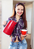 Pretty housewife with red tea kettle and cup Royalty Free Stock Image
