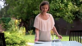 Pretty housewife serving table, waiting kids and husband for dinner outdoors royalty free stock images