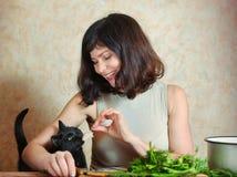 Pretty houswife cut meat feeding cat smile Royalty Free Stock Image