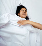 Pretty indian brunette real woman in bed smiling, white sheets, tann skin close up mulatto. cant sleep Stock Photos