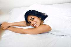 Pretty indian brunette real woman in bed smiling, white sheets, tann skin close up mulatto. cant sleep Royalty Free Stock Photo