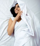 Pretty indian brunette real woman in bed smiling, white sheets, tann skin close up mulatto. cant sleep Royalty Free Stock Photography
