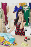 Pretty Indian female dressmaker answering phone call while standing at table Royalty Free Stock Images
