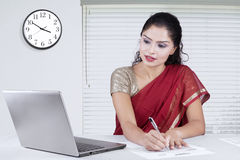 Pretty indian woman writes document in office Royalty Free Stock Images