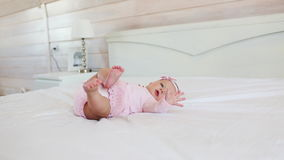 Pretty infant in pink dress lies on back on a bed at home stock video footage
