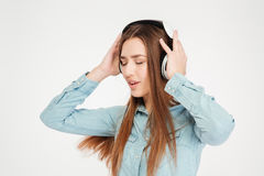 Pretty inspired woman in headphones listening to music and dancing Stock Photo