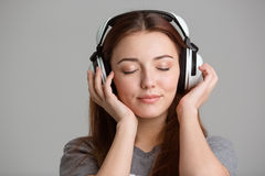Pretty inspired young woman listening to music with eyes closed Royalty Free Stock Images