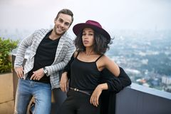 Beautiful interracial couple on balcony. Pretty interracial couple on the balcony on the background of the cityscape. Black girl in a crimson hat and her smiling Royalty Free Stock Photography
