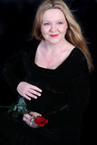Pretty Irish pregnant woman. Pretty Irish woman with blonde hair touching her pregnant belly dressed in a black velvet dress holding a  red rose Royalty Free Stock Images