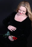 Pretty Irish pregnant woman. Pretty Irish woman with blonde hair touching her pregnant belly dressed in a black velvet dress holding a  red rose Stock Images